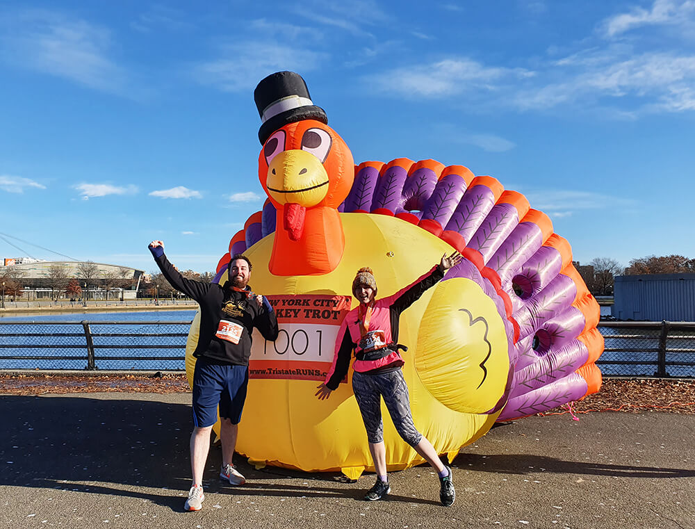 Emily and Ian celebrating after running a 5k next to a giant inflatable turkey