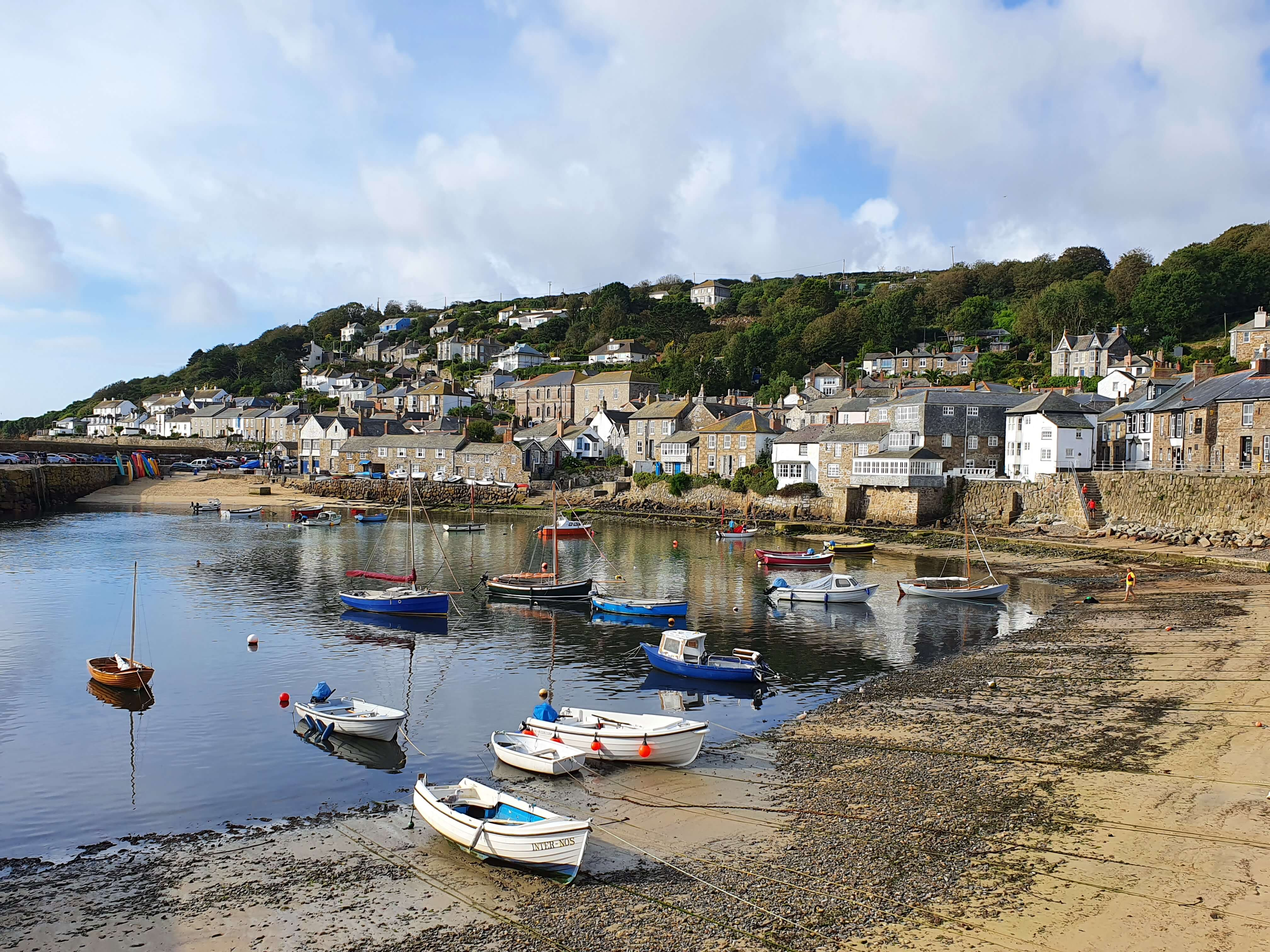 Mousehole harbour, featuring boats in the water overlooked by quaint houses and cottages