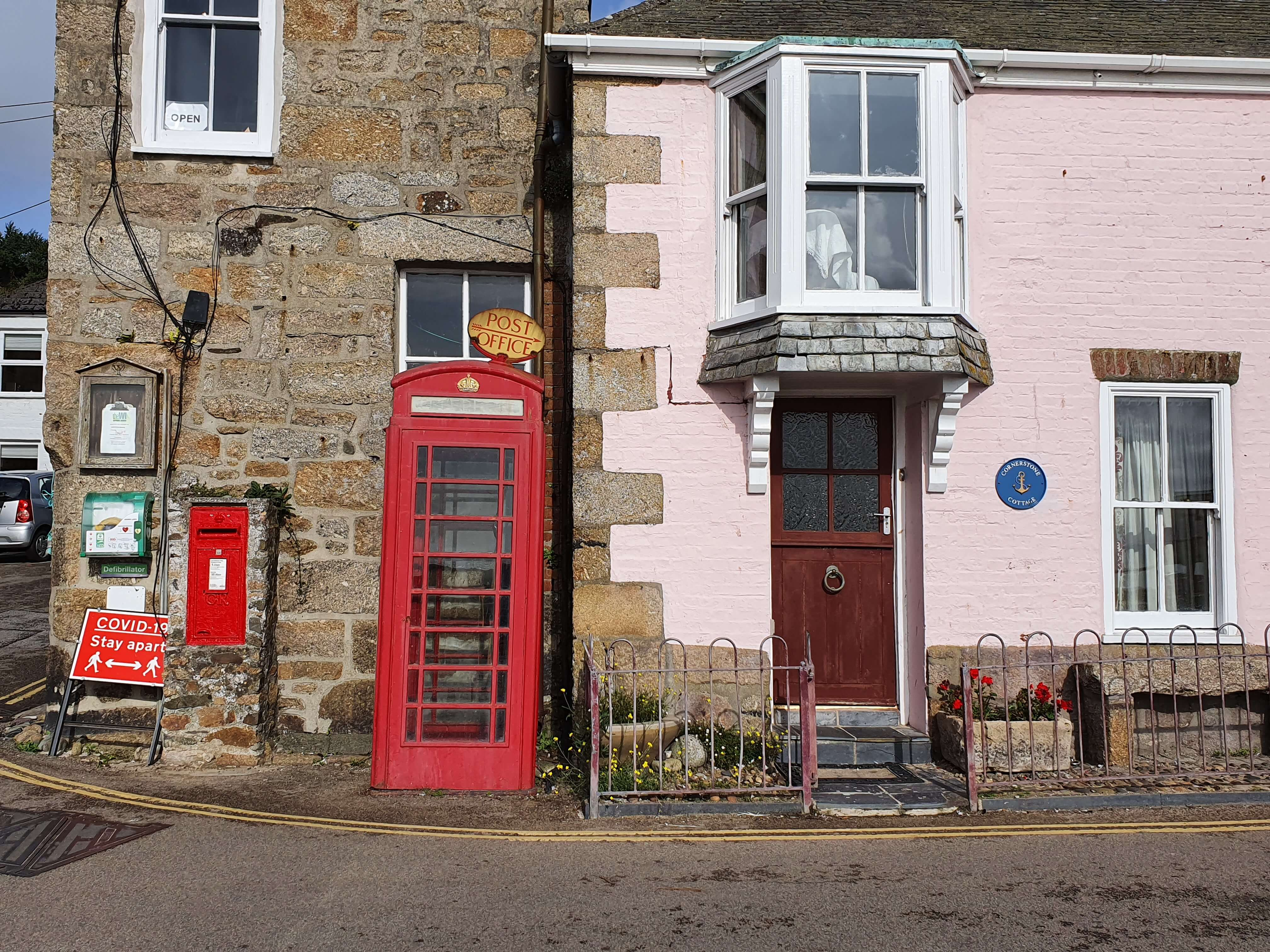 A bright red phone box in front of a pink cottage