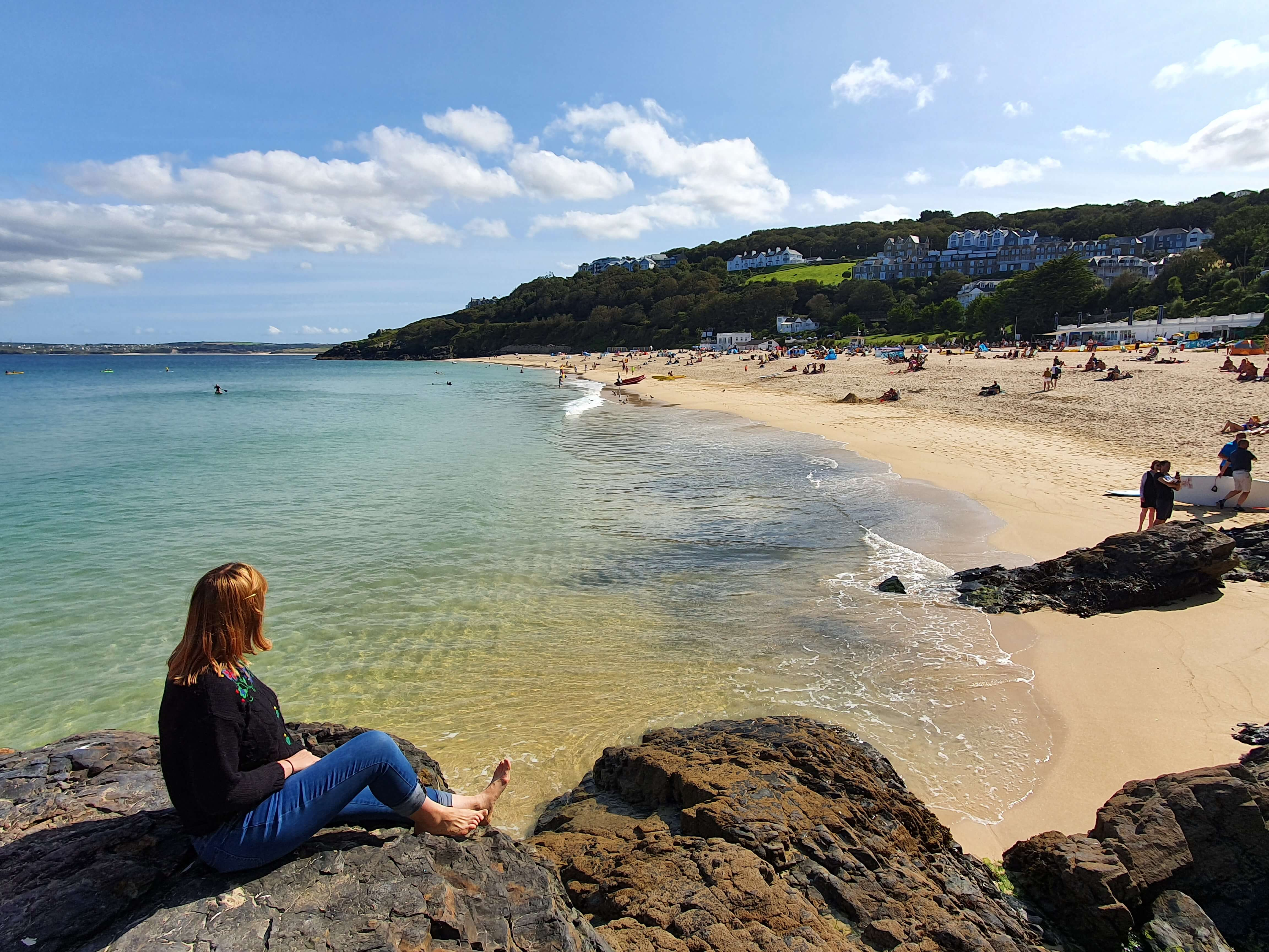 Emily sits on rocks, overlooking Porthminster Beach in St Ives