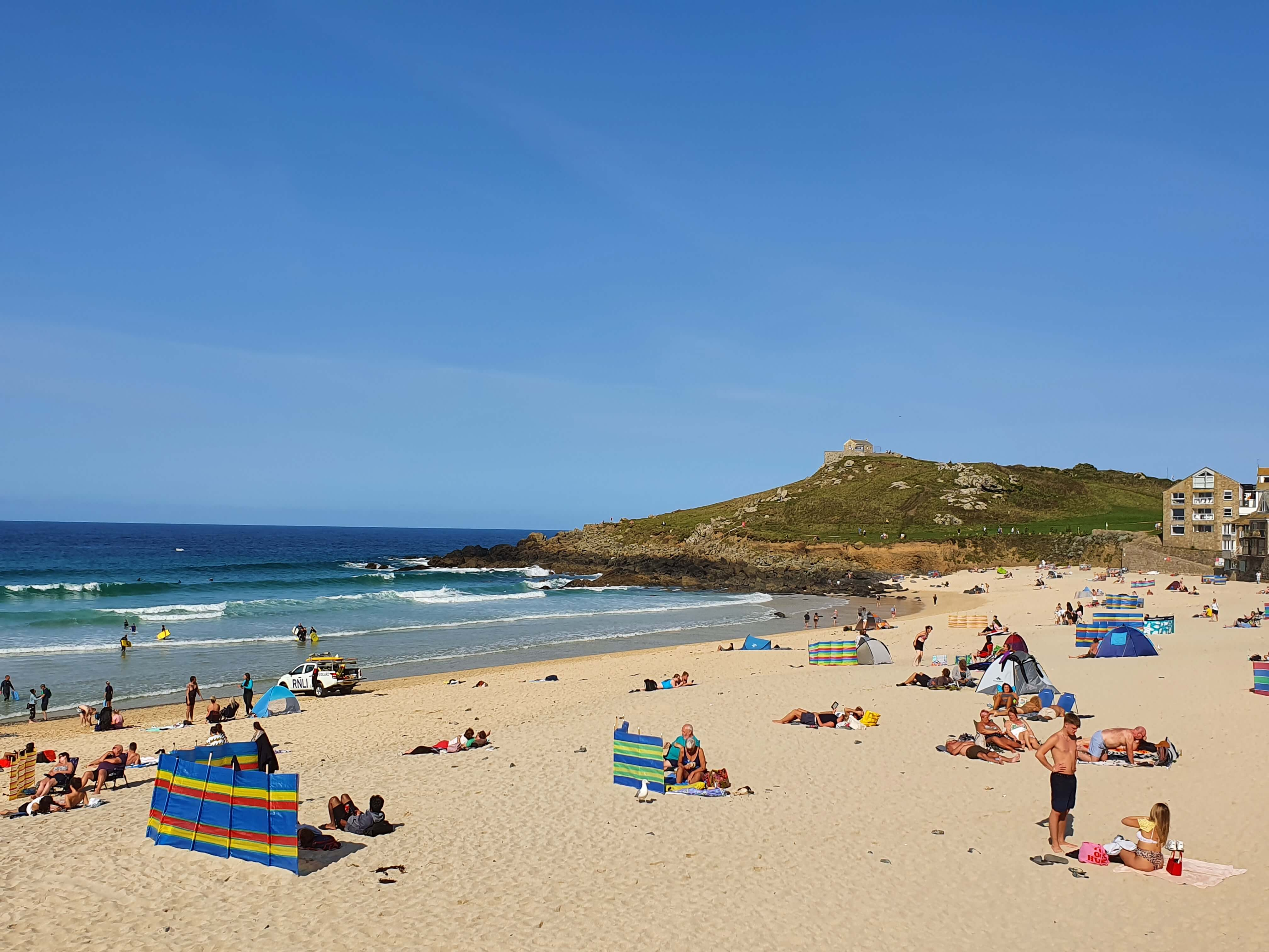 Porthmeor Beach in St Ives - pictured, people sunbathing on the white-sand beach