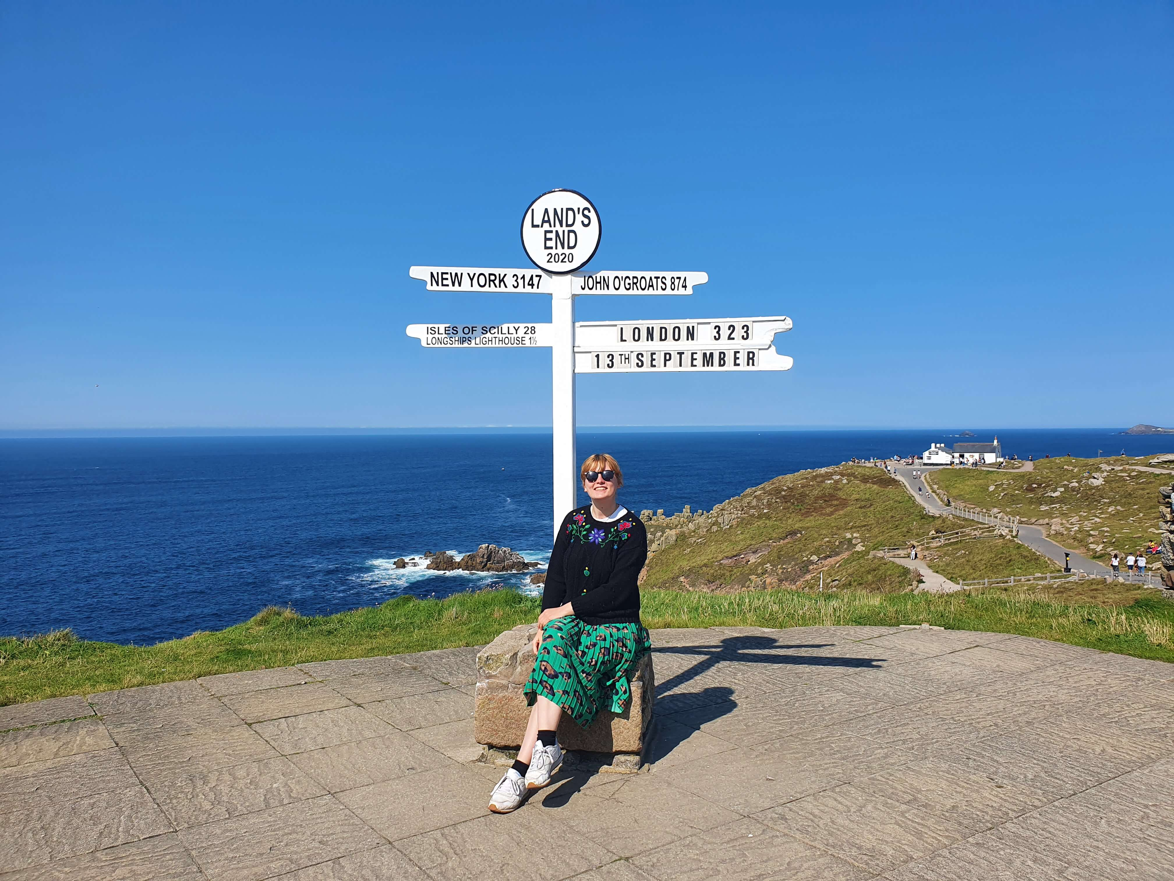 Emily sits next to a white signpost at Land's End that points out to cities including New York and London